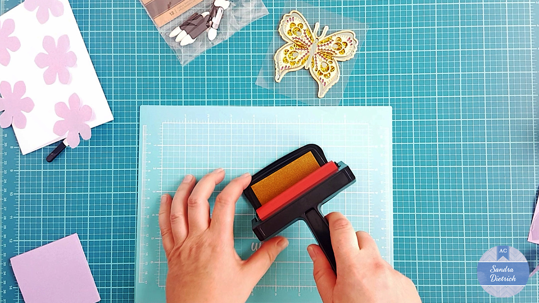 Cover the brayer with ink by rolling it over an ink pad.