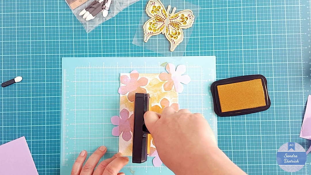 The brayer is now used to ink the cardstock base. The die-cut flowers work like a stencil.