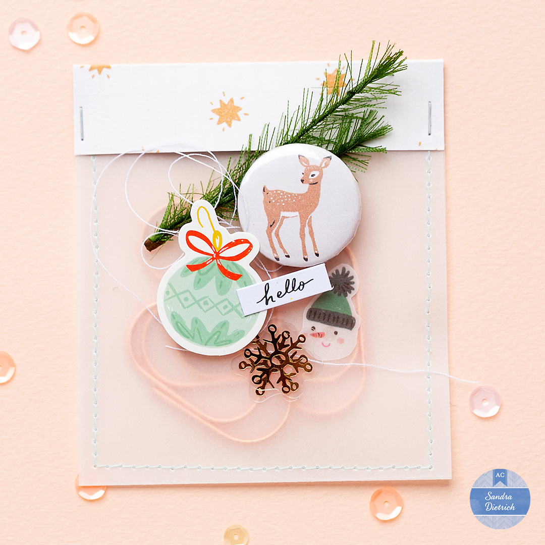 Vellum Gift Bag with embellishments from Crate Paper. The bag holds paper clips. A cute snowman, a small pine brunch, and a button flair enhance the design.