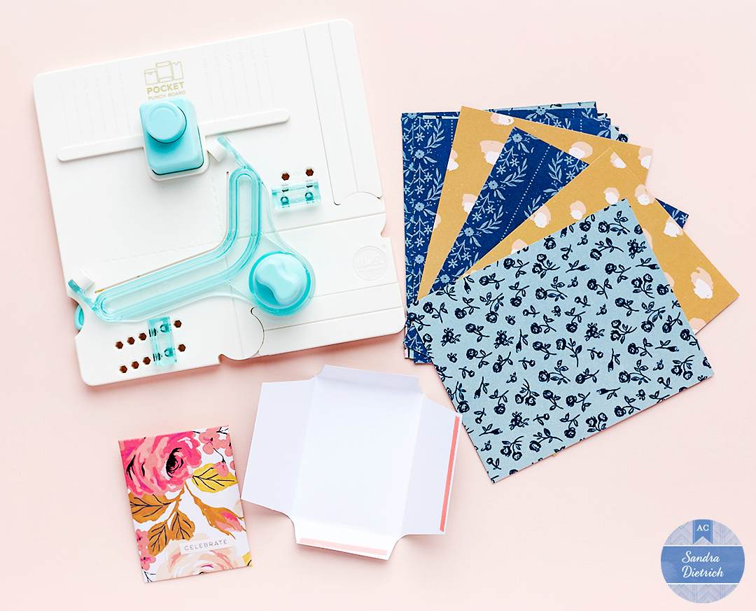 Make pockets with the Pocket Punch Board by We R Memory Keepers. Use lovely patterned papers from Marigold and glue the pockets with double-sided tape.