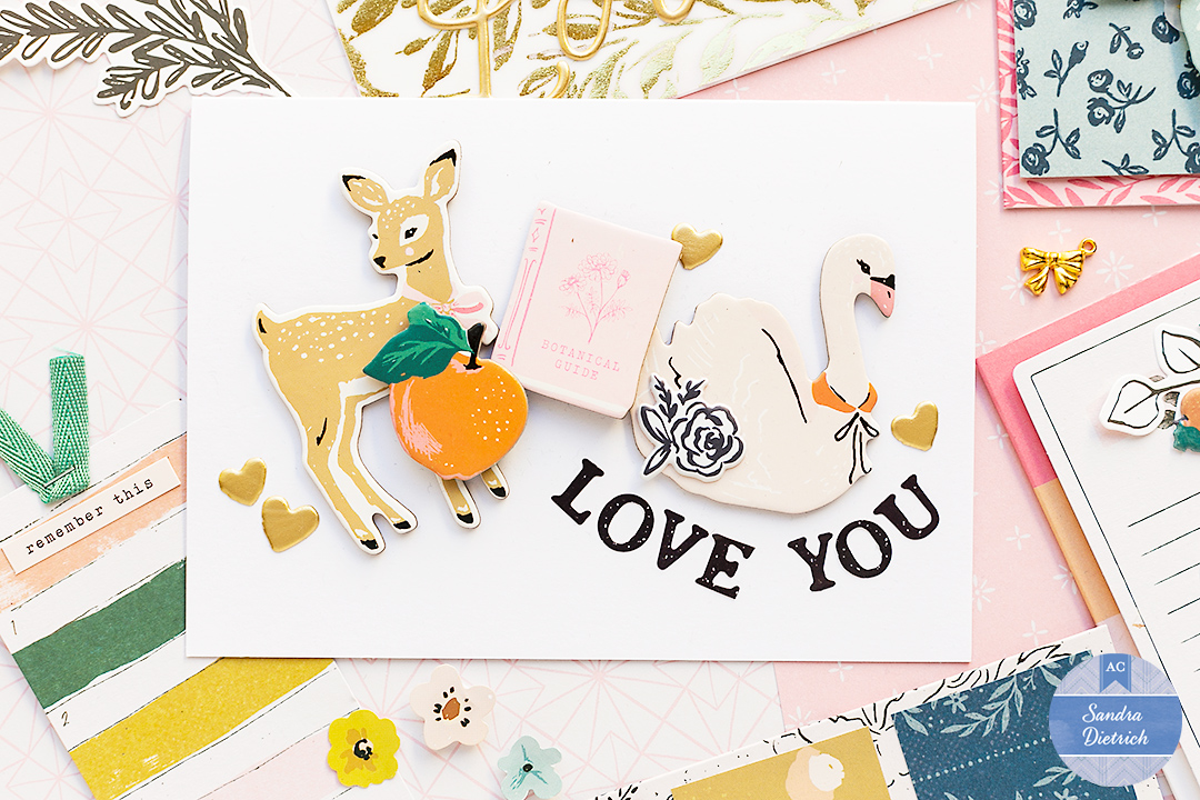 Card made with white cardstock and cute chipboard stickers from the Marigold Collection by Crate Paper. The card says LOVE YOU and a shows a deer, a book, a swan, an apple, and some heart stickers.