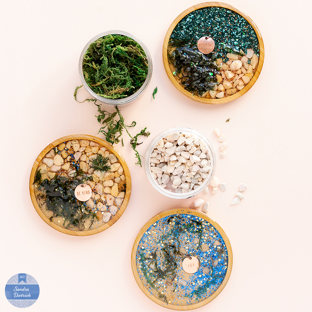 Create decorative Color Pour Resin Wood Coasters with Sandra Dietrich. Add moss, pebbles, and other embellishments to create a fancy table decoration