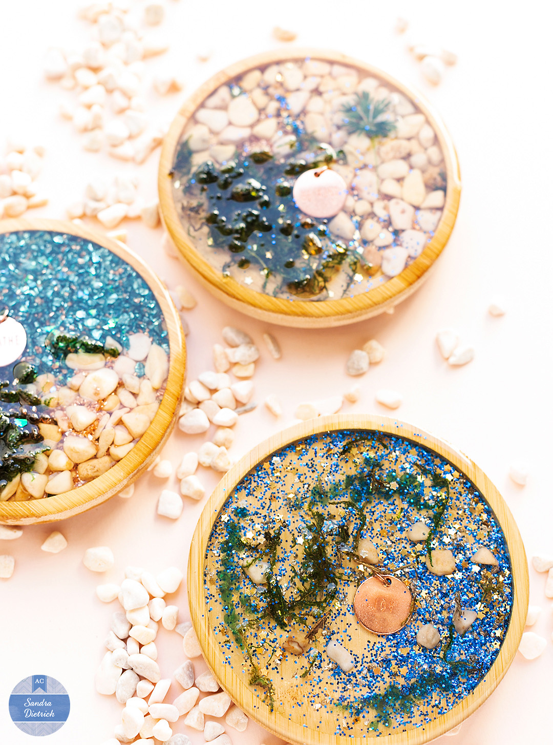 Three wood coaster filled with resin, charms, glitter, pebbles, moss. The shiny look makes these coasters special.