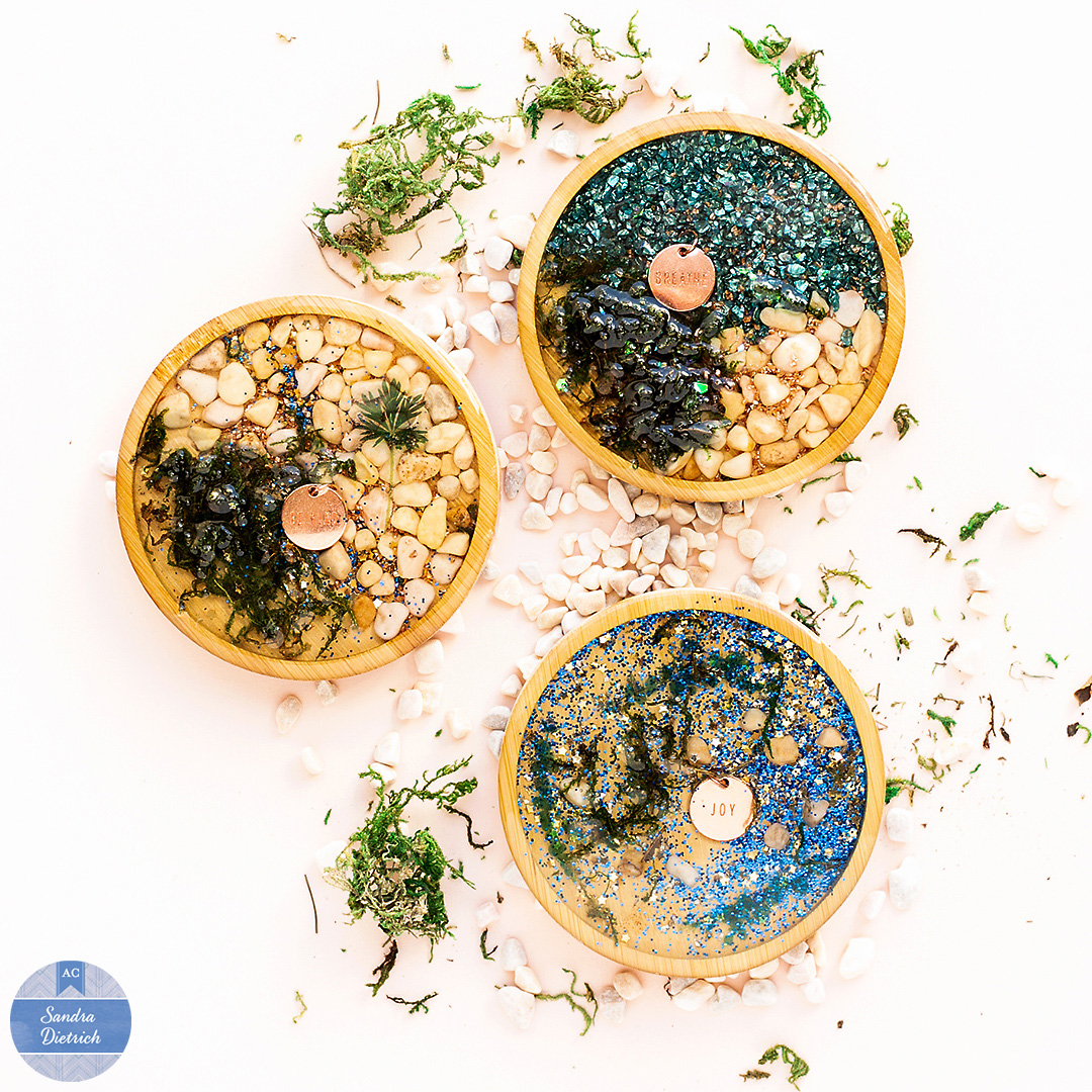 Decorative wood coasters with crushed glass, charms, pebbles, stickers, and star sequins. The coasters are made with the Color Pour Resin Collection by American Crafts.
