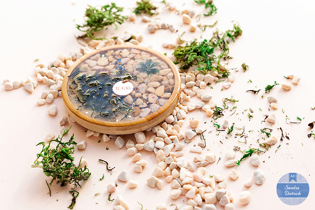 Create a great table decoration with pebbles, moss, wood coasters and the Color Pour Resin Collection.